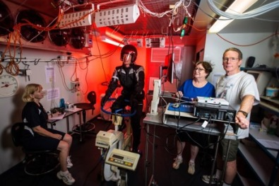 Testing motorcycle in the thermal chamber (from left) research assistant Liz Taylor, volunteer rider Dr Greg Peoples, Liz de Rome and Nigel Taylor.