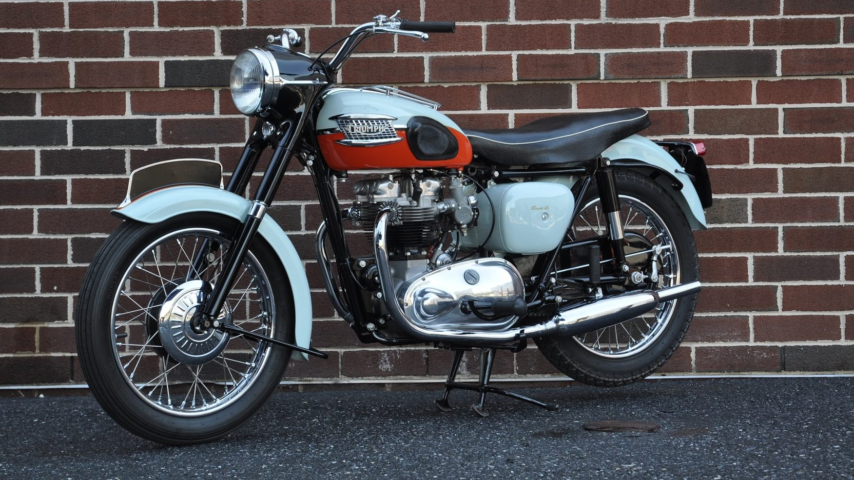 1959 Triumph Bonneville T120 Parked In Front Of A Brick Wall