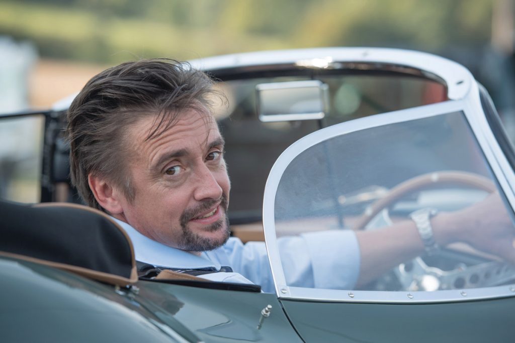 a view of Hammond on the Grand Tours show, in a car, turning around and smiling at the camera
