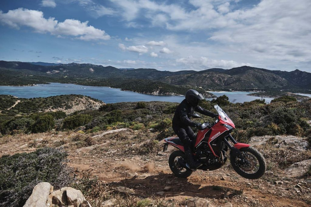 A view of a rider trying out the all-new Moto Morini X-Cape adventure motorbike on rugged terrain, with a gorgeous tropical view.