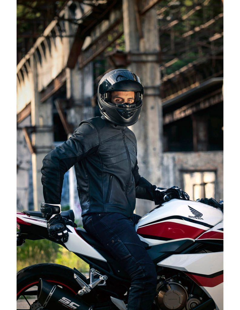 A view of a rider on a motorcycle wearing the new Neowise vegan leather motorcycle jacket from Andromeda Moto
