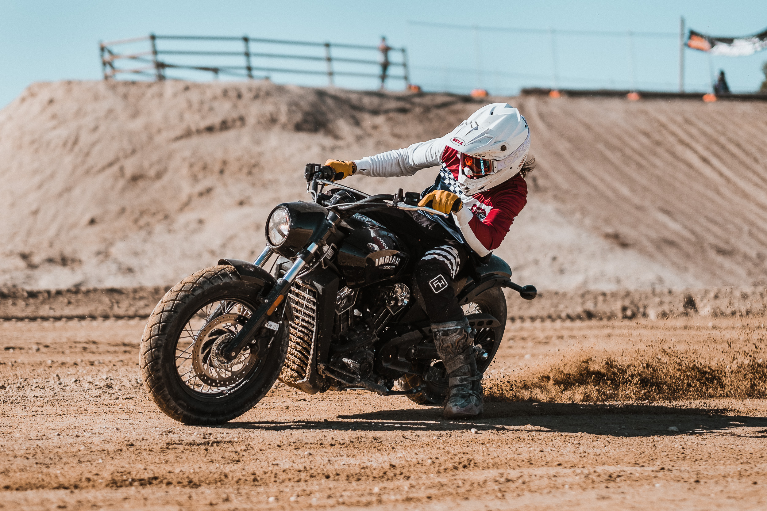A motorcycle rider on an Indian Scout races on a dirt flat track circuit