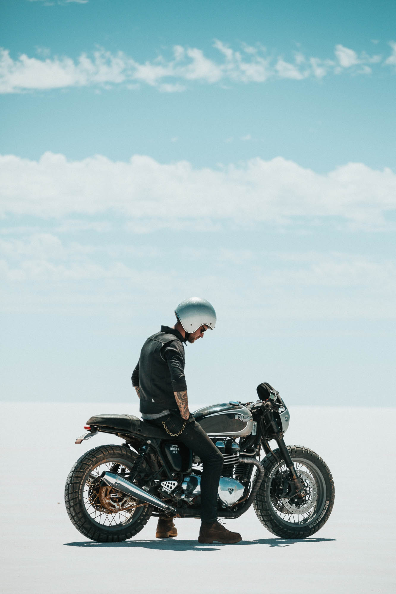 A man sits on a custom Triumph Motorcycle on a salt flat in Australia