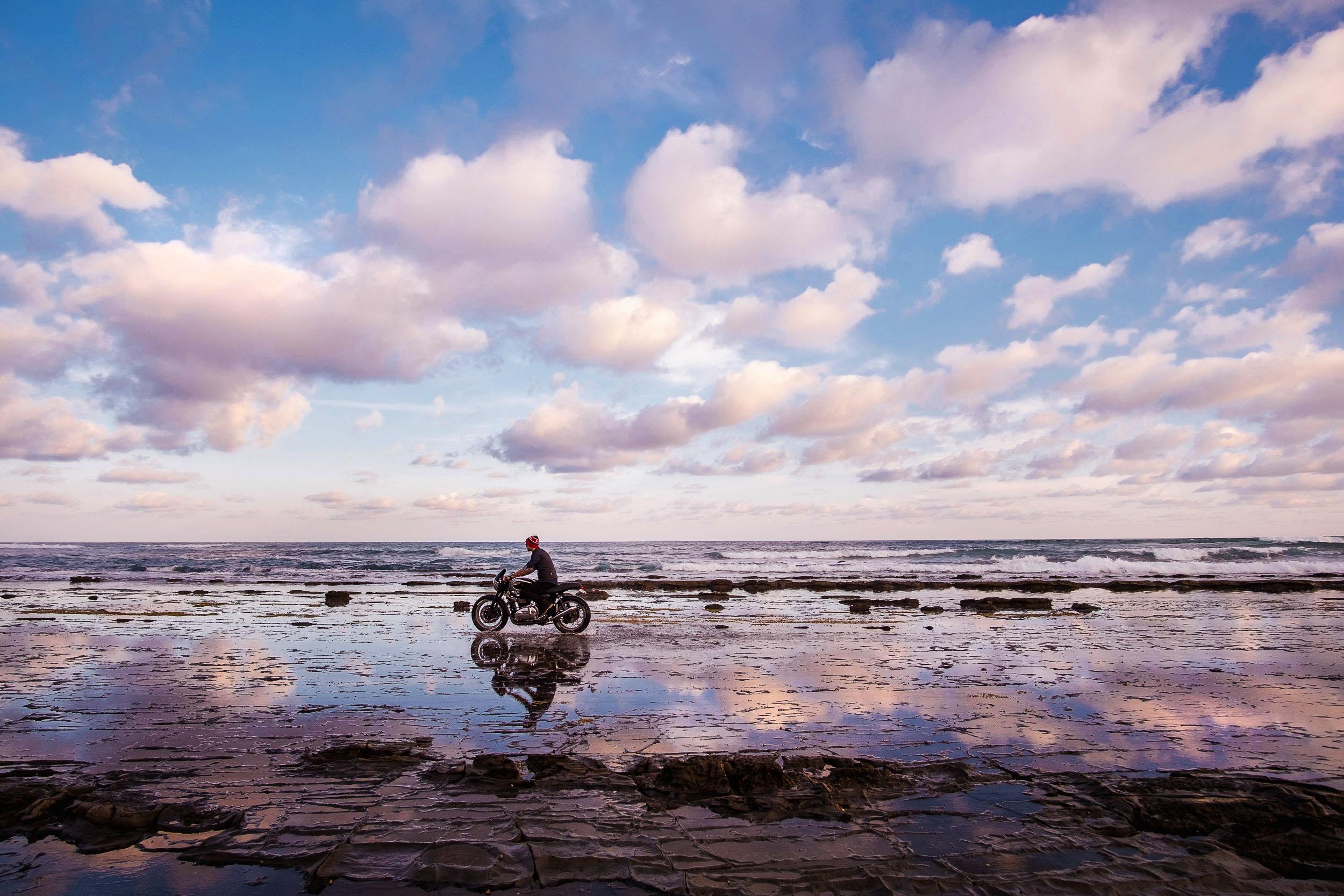 A motorcycle rider on an Aussie beach at dusk