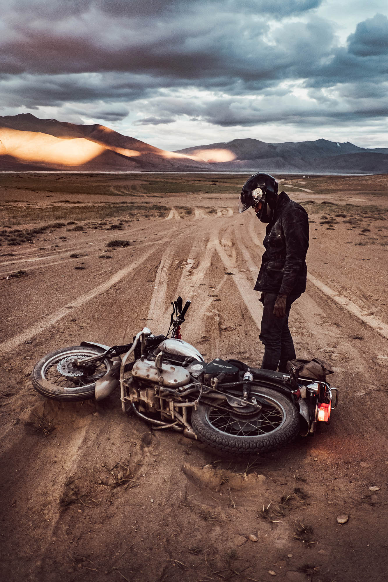 A motorcycle rider looks down at his fallen bike on a majestic road in the Rajasthan desert