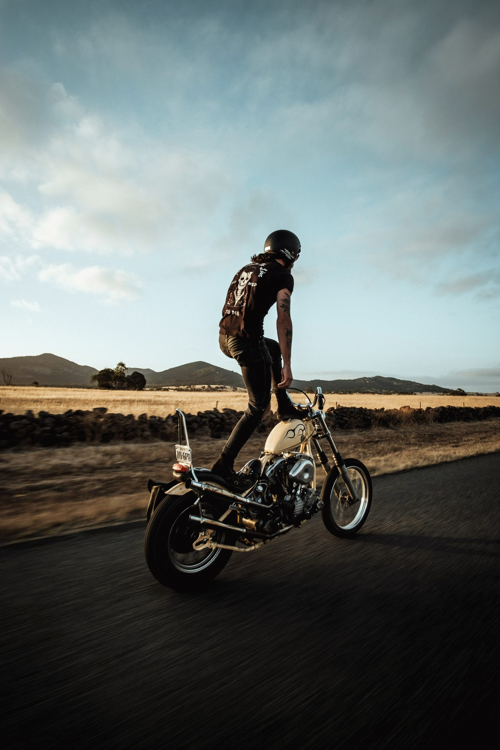 A Harley chopper rider in rural Australia stands upright on his bike as it travels down the road