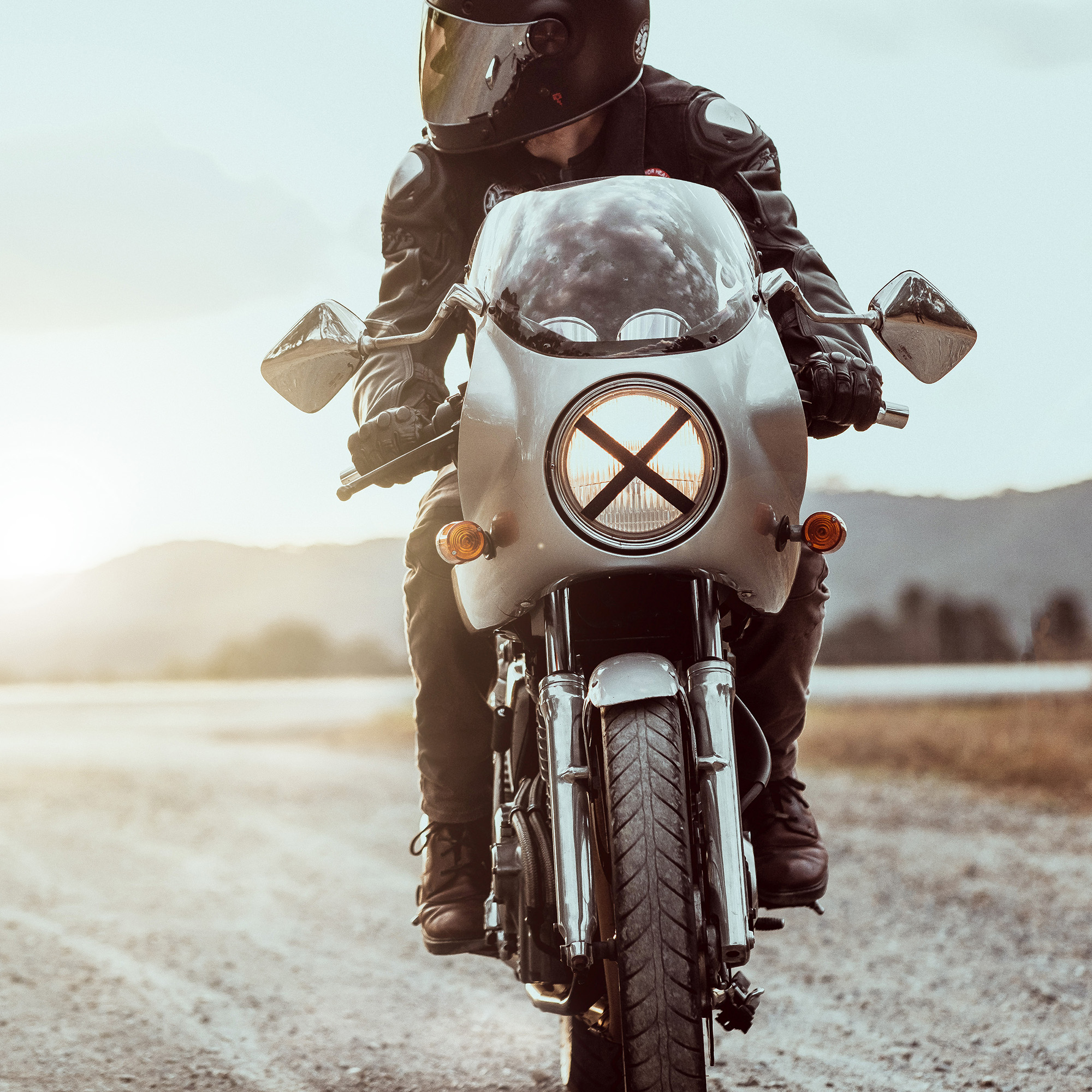 A cafe racer motorcycle and rider tackles a dirt road in Australia