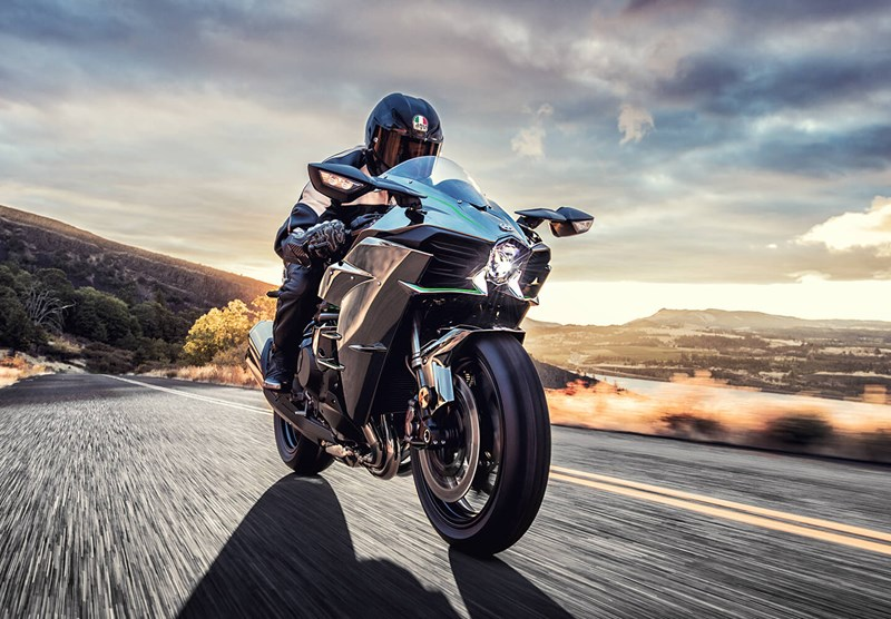 An image of a rider cruising down a road on the Ninja H2R
