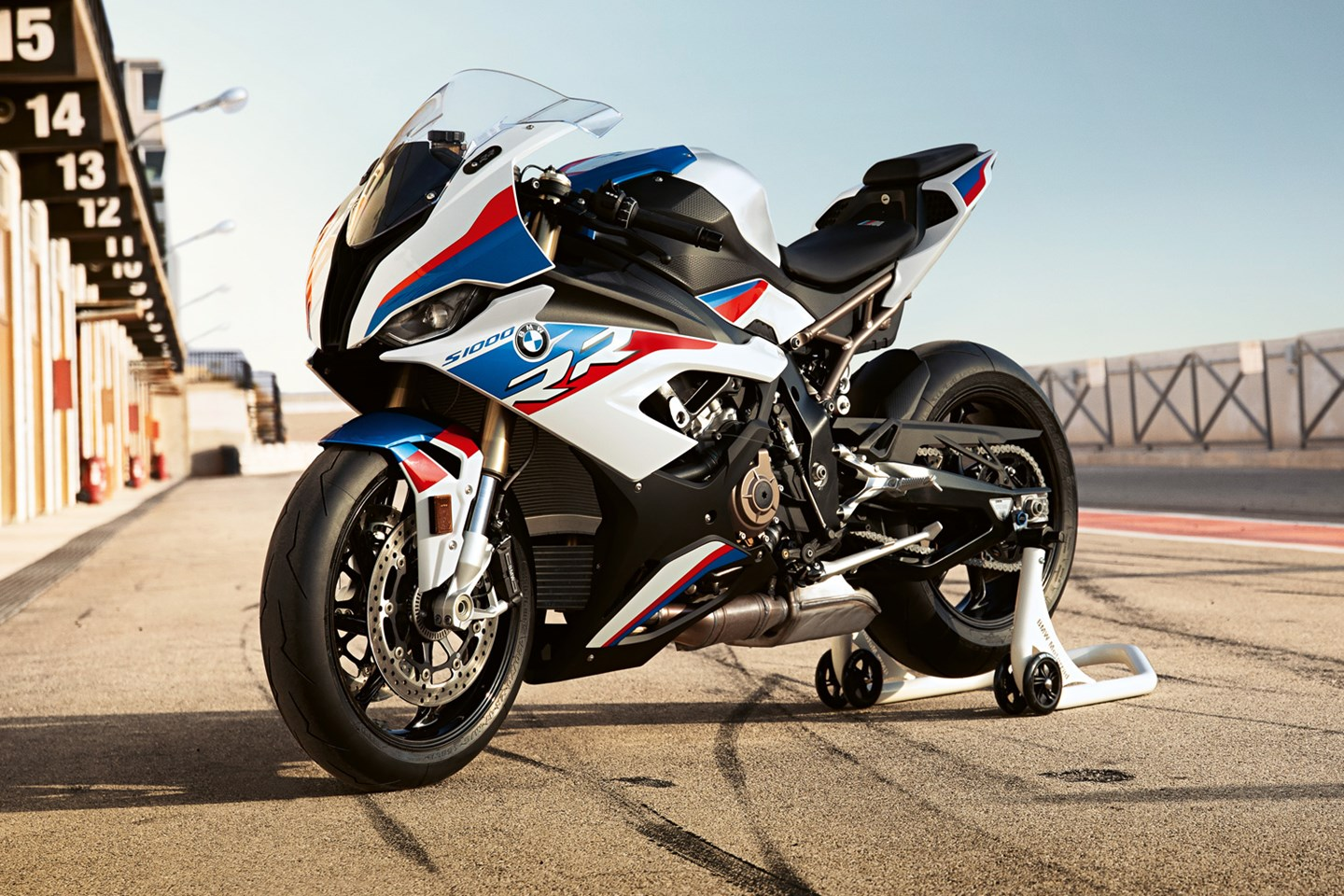 A BMW S1000RR motorcycle in the pits at a racetrack at dusk